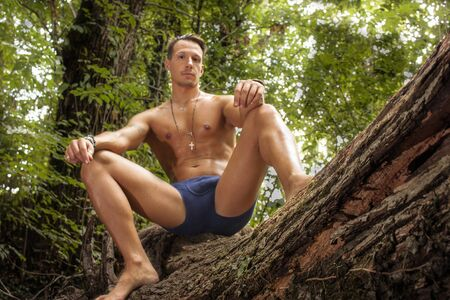 Boy laying in underwear in the woods i a photo session