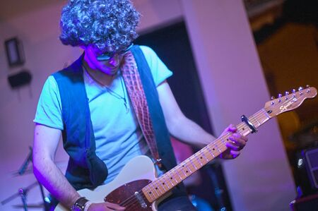 Guitarist under colored lights during a live performance
