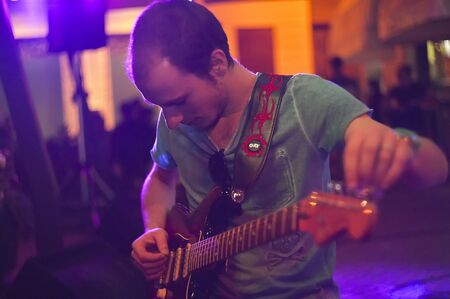 Blues Guitarist night live under colored lights