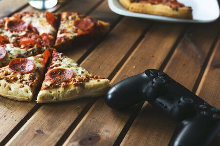 Games and pizza: evocative image with a joystick and pizza slice
