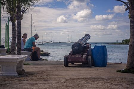 BAYAHIBE, DOMINICAN REPUBLIC 21 JANUARY 2020:Couple of tourists sitting on the bench look at the sea in Bayahibe
