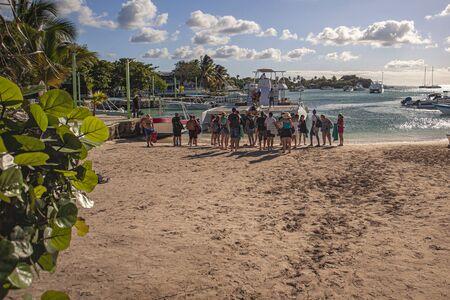 BAYAHIBE, DOMINICAN REPUBLIC 21 JANUARY 2020: Catamaran full of tourists arrives on Bayahibe beach