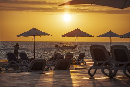 Parasols and sunbeds create a sunset silhouette on Dominicus beach in the Dominican Republic with a motorboat in the sea