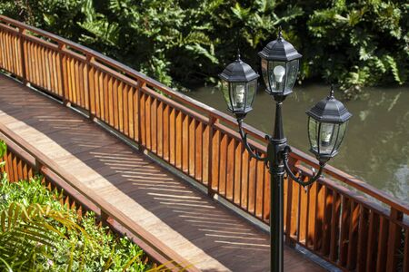 Small wooden bridge over the lake with a lamp