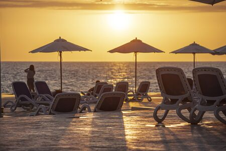 Parasols and sunbeds create a sunset silhouette on Dominicus beach in the Dominican Republic