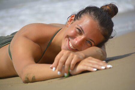 Smiling and happy Teenager in bikini lying by the sea Standard-Bild - 143158848