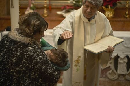 Old Catholic priest celebrates baptism in an Italian Church