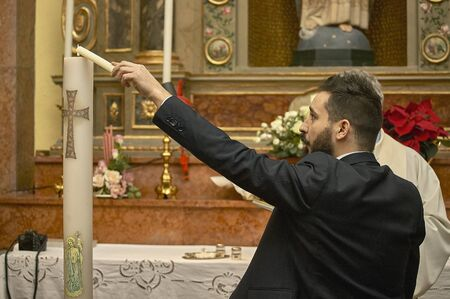 Godfather at baptism holds and lights the candle, symbol of a part of the Christian ceremony