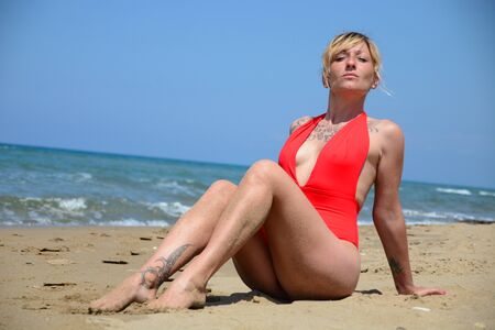 Rebel blonde girl poses sitted in red swimsuit at the beach 写真素材
