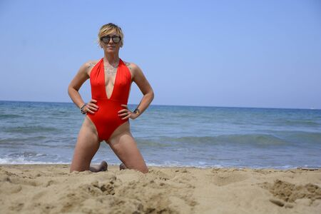 Rebel blonde girl poses in red swimsuit at the beach Foto de archivo