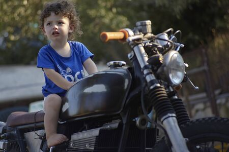 Portrait of Baby sitted on old motorbike happy and smiling 写真素材