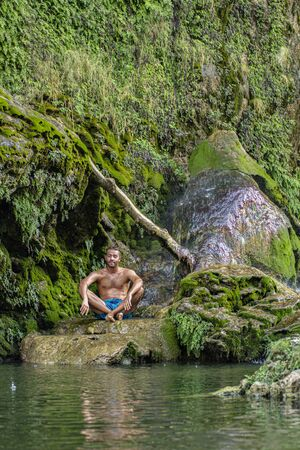 Meditating boy under the waterfall immersed in nature
