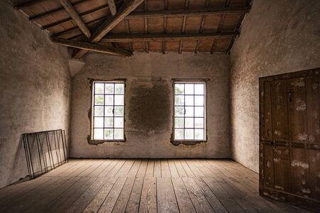 Pièce vide dans une maison abandonnée avec fenêtre et parquet