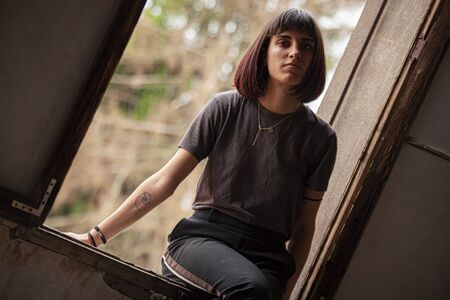 Brunette girl sitted on a window of an old and abandoned house 写真素材