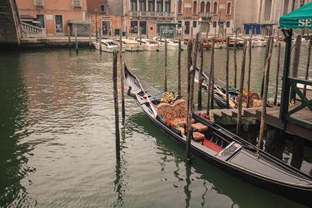 Two Gondolas moored in Venice in Canal Grande during a cloudy day