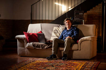 Man sitted on sofa in the living room using his laptop