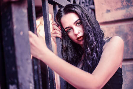 Sad girl portrait clinging to a gate with cold colors