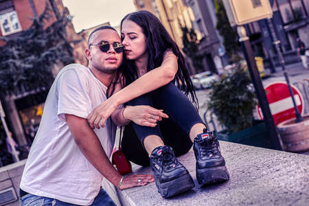 Young Love Couple sitting on a low wall in the city Archivio Fotografico