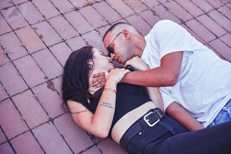 Young Love Couple lying on the ground in the city Archivio Fotografico
