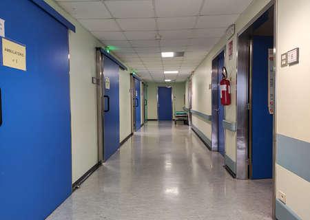 Empty Hospital corridor with blue doors and white illumination