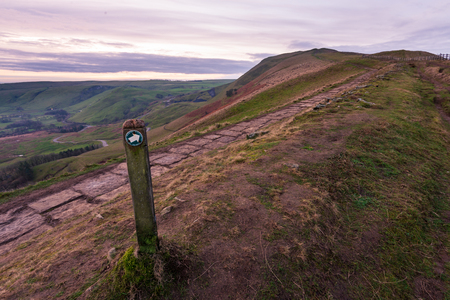 A view of Mam Tor in the Peak District early morning as the sun is rising over the hill