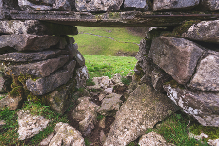 A view of the Peak District through a hole in a wall made from rocks and stones in the UK