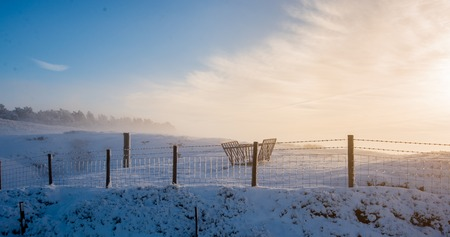 A snowy hill during a foggy sunrise in the Peak District after a snow storm 版權商用圖片