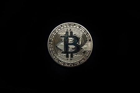 Physical gold Bitcoin isolated against a black background