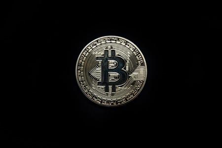 Physisches Gold Bitcoin vor schwarzem Hintergrund isoliert