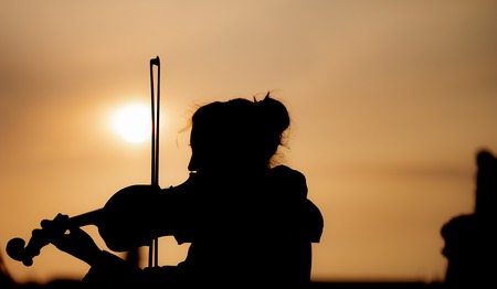 Silhouette of female playing the violin during sunset against the sun - Taken in Prague Reklamní fotografie - 120871419