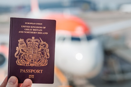 A red British passport held up against a background of a generic plane on a bright sunny day