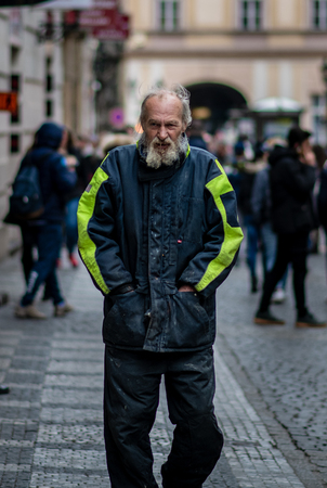 A homeless man covered in drool and dirt walks through the streets of Prague on a cold spring day Editorial