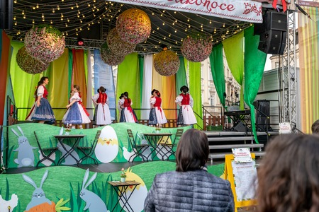 PRAGUE, CZECHIA - 10TH APRIL 2019: Crowds watch School children perform on stage during Pragues Easter Market celebrations in the Old Town Sqaure