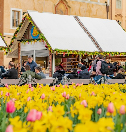 PRAGUE, CZECHIA - 10TH APRIL 2019: Crowds at Easter Market in Prague old town square surrounded by flowers daffodils