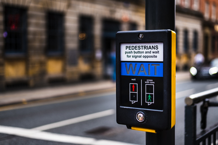 Pedestrian Crossing button in Leeds City Centre that says WAIT for people to cross the road