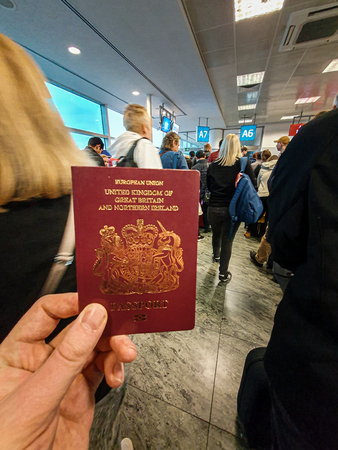 A white male holds his red British Passport in his hand in the middle of a crowded departure terminal