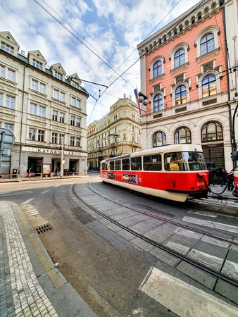 The bright red tram in Prague carries customers around the city on a bright sunny day in April