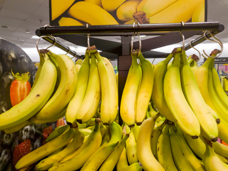 Bunches of yellow Banannas for sale inside a shop Stock Photo