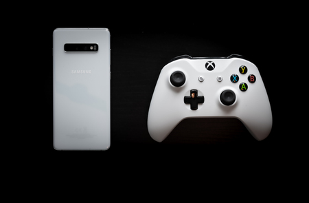 A phone and controller sit side by side as gaming becomes multi-platform Stock Photo - 124913142
