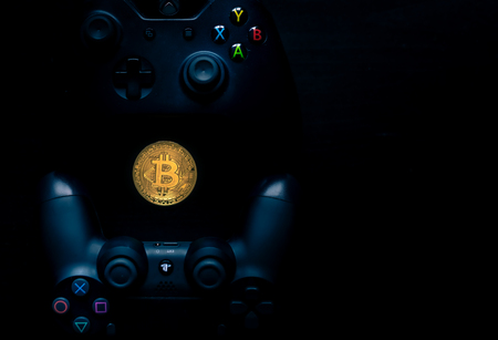 Playstation and Xbox controllers next to a physical Bitcoin. Editorial