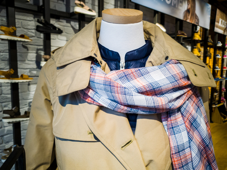 Un maniquí muestra la última bufanda y chaqueta fasionable en una tienda Foto de archivo