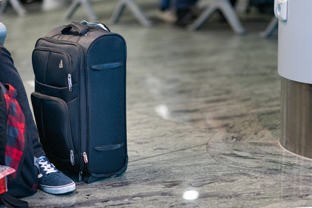 A suitcase sits next to a tourist at an airport as the wait to board a plane at Prague International Airport Editorial