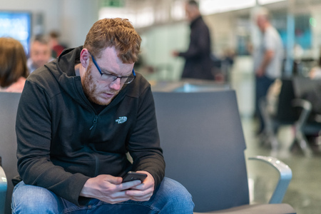 A man sits in an airport departure terminal texting his loved ones waiting for his next flight back home
