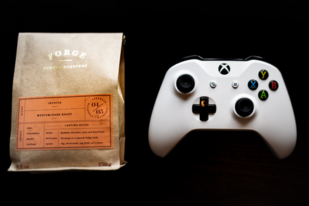 Xbox One games controller sat next to a bag of ground coffee against a dark black background Editorial