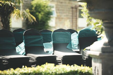 Black chairs with a blue ribbon around them sit outside waiting for guests at a wedding in Summer 写真素材 - 129398391