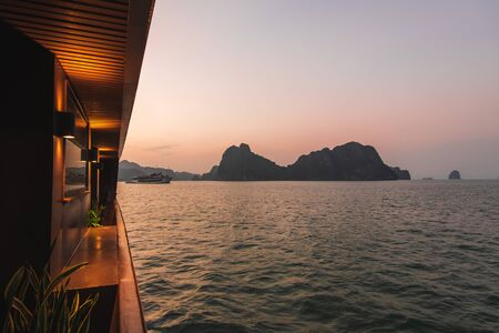 Ha Long Bay in Vietnam during a beautiful Sunset with calm, tranquil seas. Shot in Autumn 2019 from a cruise ship tour