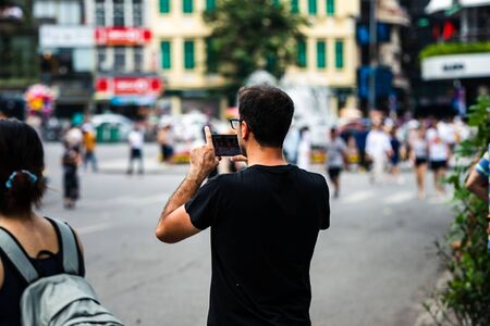 A proud and happy caucasian father records his sons dance performance on a smart phone in an Asian City during a hot day