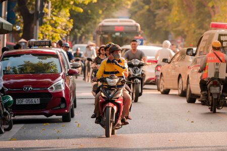 Hanoi, Vietnam - 11th October 2019: A driver and his passenger drive on a moped through the busy streets of Hanoi during sunset driving towards the camera Редакционное