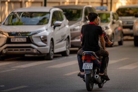 Hanoi, Vietnam - 11th October 2019: A driver and his passenger drive on a moped through the busy streets of Hanoi during sunset driving way from the camera Фото со стока - 139865756