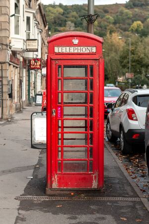 Matlock, UK - 6th October 2018: An old bright British iconic red telephone box in the middle of the frame in an English town